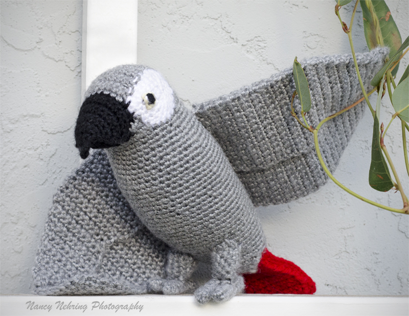 Crocheted African grey parrot amigurumi sitting on an outdoor trellis. Made by Noelle Oguri.